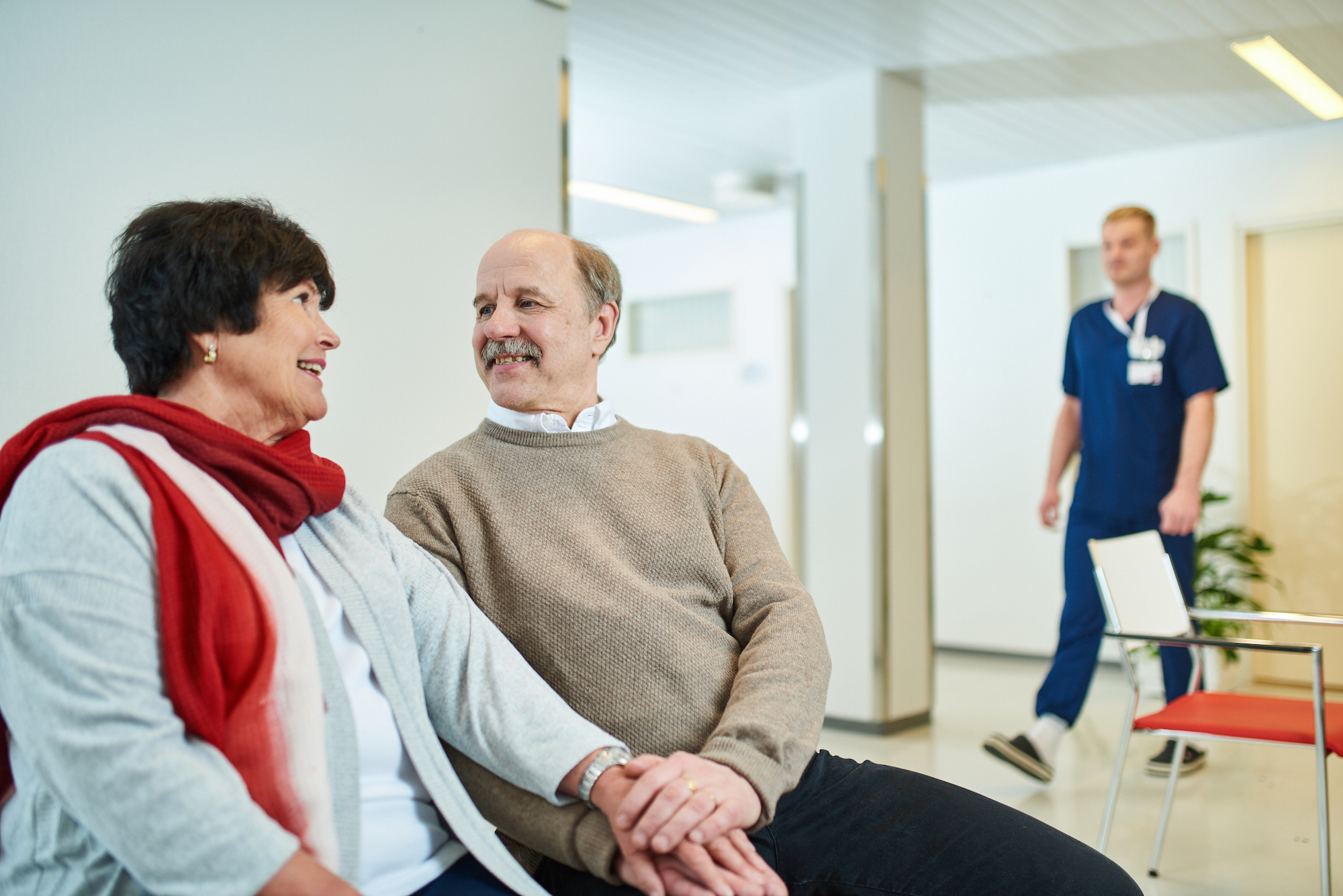 Pariskunta ja hoitaja sairaalan odotustilassa