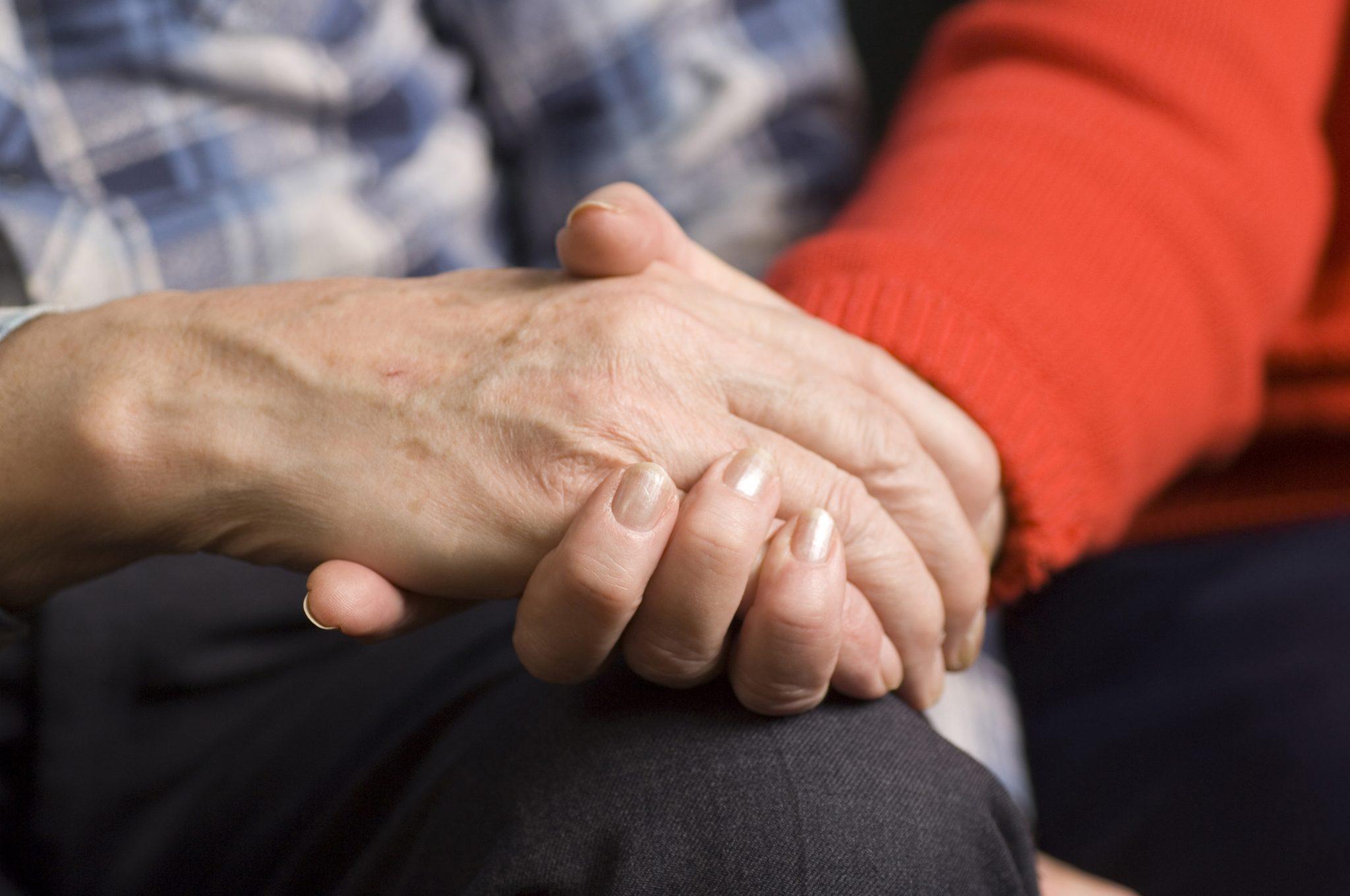Kahden aikuisen kädet yhdessä
