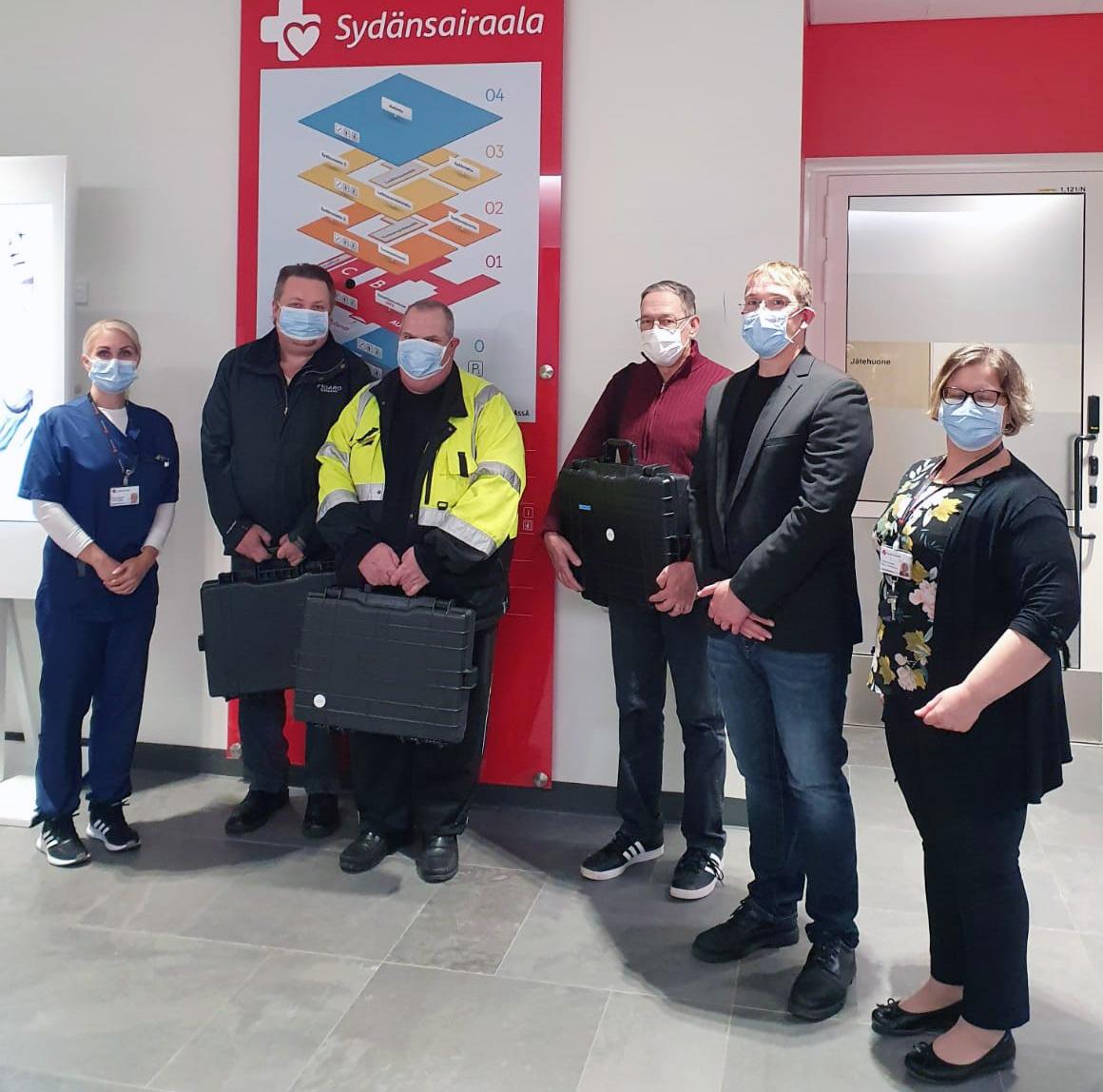 Ryhmäkuvassa Sydänsairaalan sairaanhoitaja, kehitysjohtaja ja projektipäällikkö sekä kolme asiakasta
