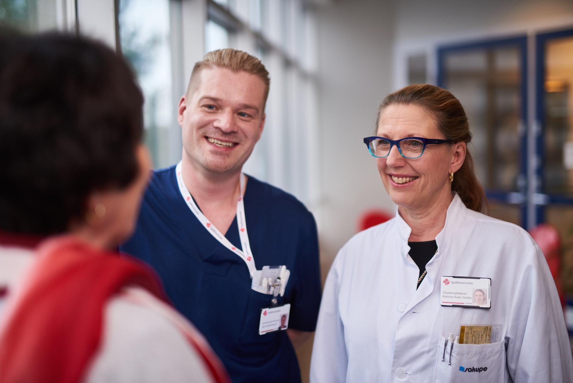 Potilas, hoitaja ja lääkäri keskustelevat aulassa