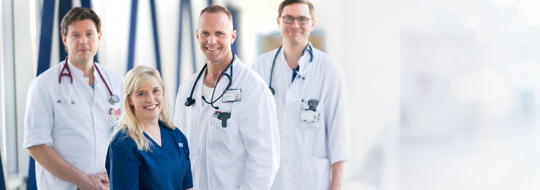Lääkäreitä ja hoitaja käytävällä
